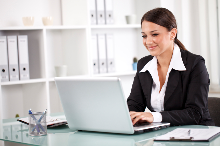 Smiling successful businesswoman working on laptop